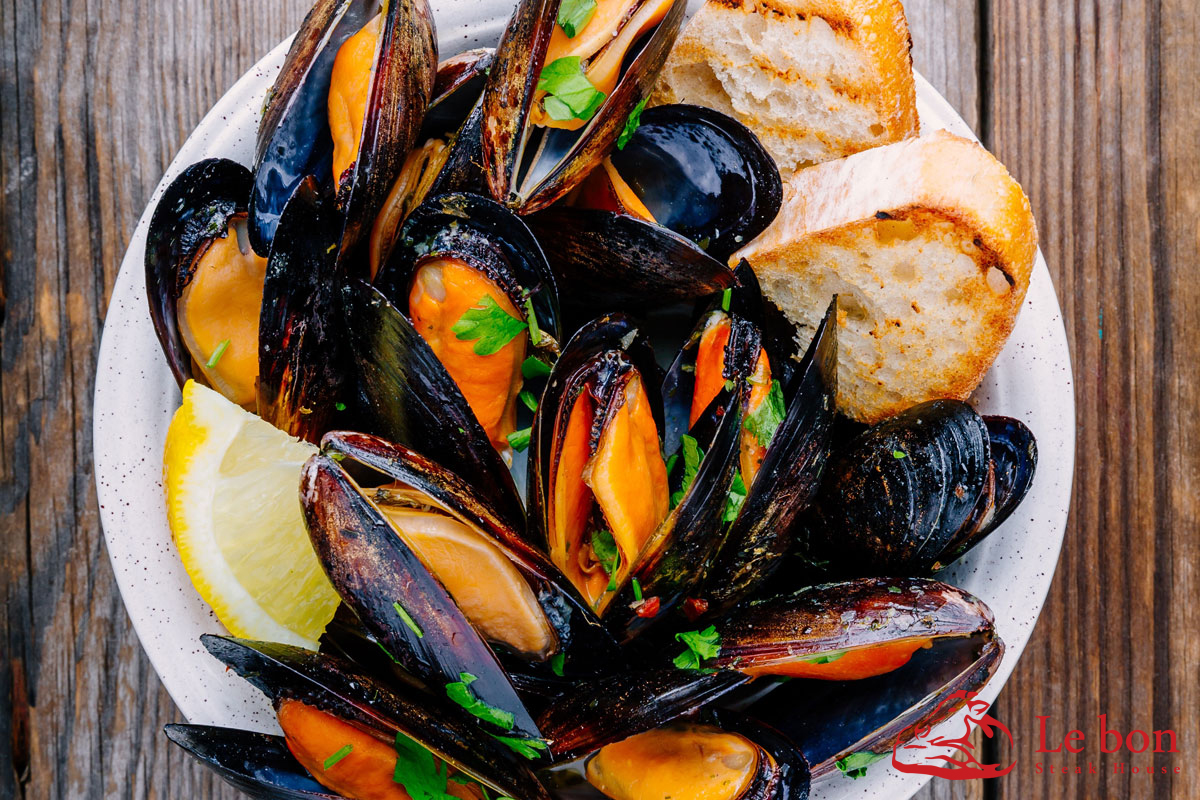 Delicious seafood mussels with with sauce and parsley.  Lemon an